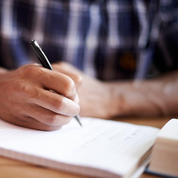 Człowiek robi notatki wzeszycie