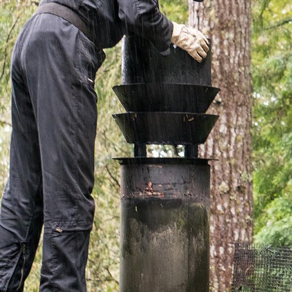 Kominiarz przeprowadza konserwację przewodów kominowych